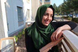 Nainen hymyilee auringon paisteessa