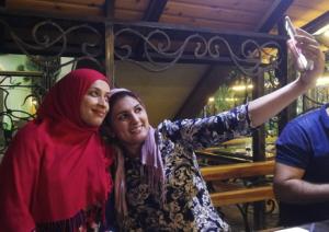 kuvassa kaksi huivipäistä naista ottaa selfietä