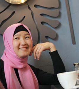 Hymyilevä nainen, jolla on päässään vaaleanpunainen huivi.