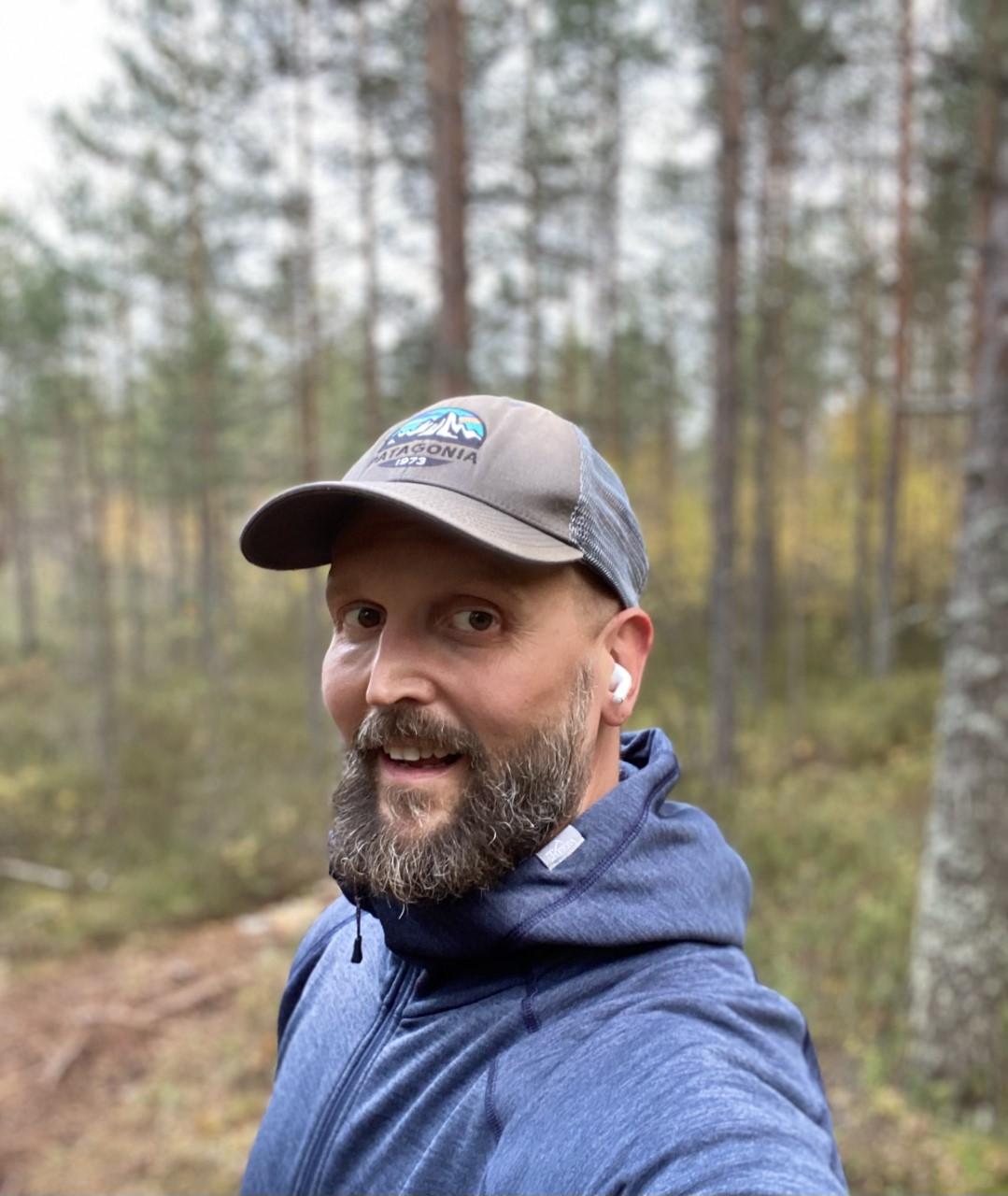 Kuvassa on lippalakkipäinen mies metsämäisemassa.