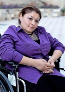 Nainen liila takki päällään istuu pyörätuolissa ja katsoo kameraan